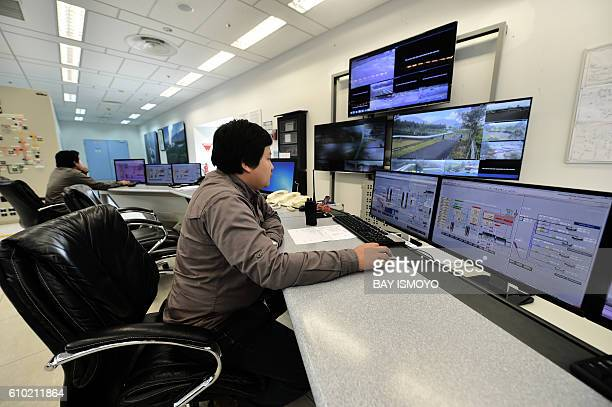This picture taken on August 31 2016 shows plant controllers working in the control room of the Wayang Windu geothermal power station on West Java in...
