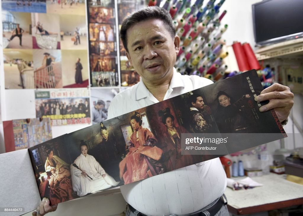 This picture taken on August 31, 2017 shows Taiwanese 'qipao' maker Chen Chung-hsin displaying his fashion designs for the movie 'The Assassin' at his studio in Taipei. Known for creating costumes for movies including Taiwanese director Hou Hsiao-hsien's Cannes-winning martial arts epic 'The Assassin', Chen learned his skills from his father and inherited his shop. / AFP PHOTO / SAM YEH / TO GO WITH Taiwan-China-fashion-culture-qipao,FEATURE by Amber WANG