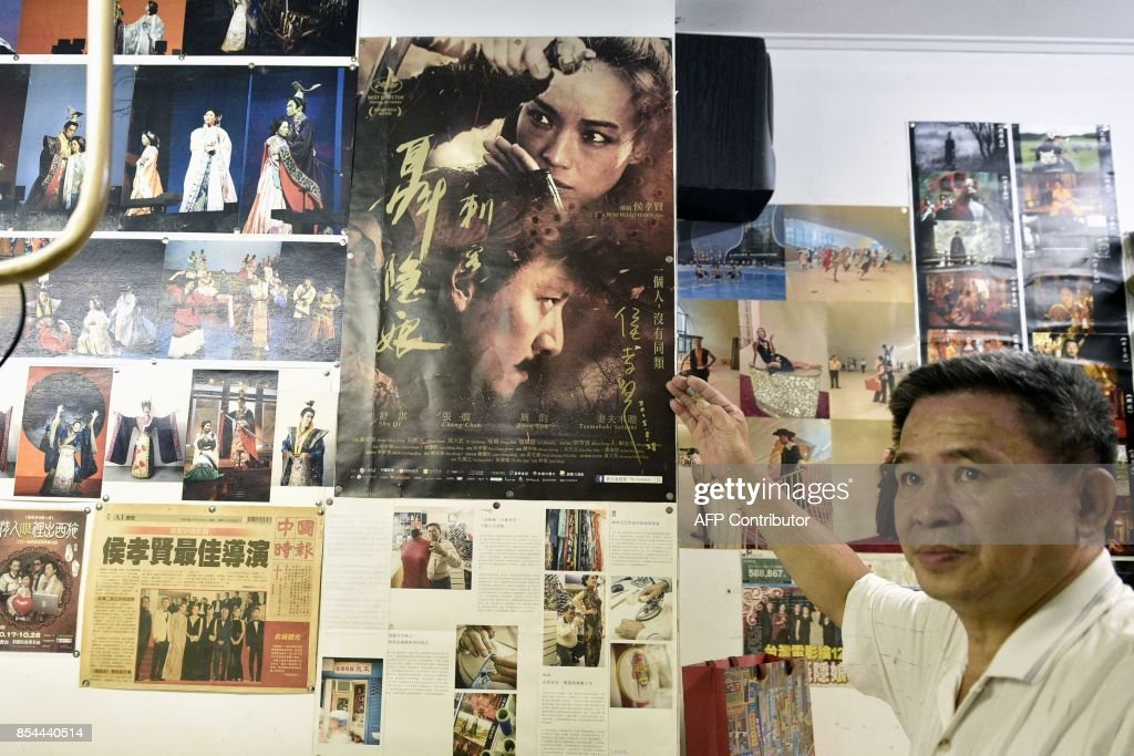 This picture taken on August 31, 2017 shows Taiwanese 'qipao' maker Chen Chung-hsin pointing at a movie poster for 'The Assassin' at his studio in Taipei. Known for creating costumes for movies including Taiwanese director Hou Hsiao-hsien's Cannes-winning martial arts epic 'The Assassin', Chen learned his skills from his father and inherited his shop. / AFP PHOTO / SAM YEH / TO GO WITH Taiwan-China-fashion-culture-qipao,FEATURE by Amber WANG