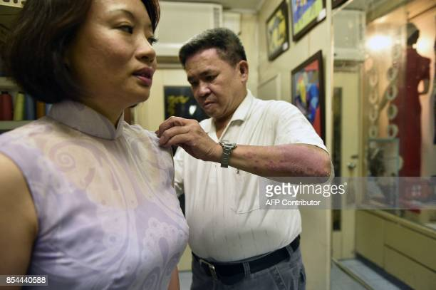 This picture taken on August 31 2017 shows Taiwanese 'qipao' maker Chen Chunghsin adjusting a 'qipao' on a customer at his studio in Taipei Known for...