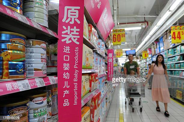 This picture taken on August 4 2013 shows a family selecting baby formula in the imported baby products section of a supermarket in Beijing New...