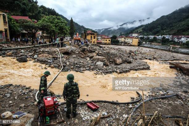 This picture taken on August 4 2017 shows soldiers operating a water pump amid destruction caused by flash floods in the mountainous town of Mu Cang...