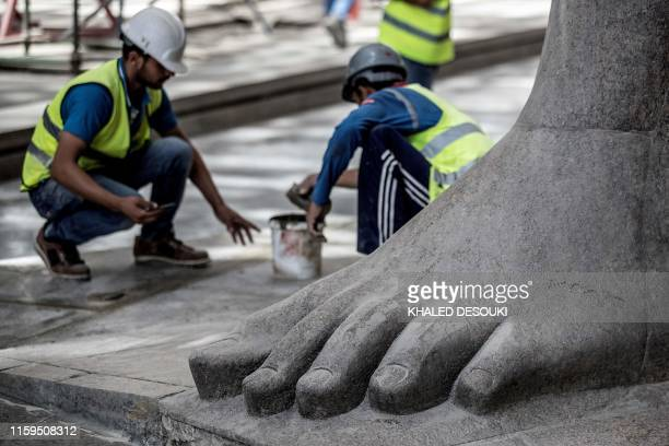 This picture taken on August 4, 2019 shows a feet of the 3,200-year-old pink-granite colossal statue of King Ramses II at the entrance of the Grand...