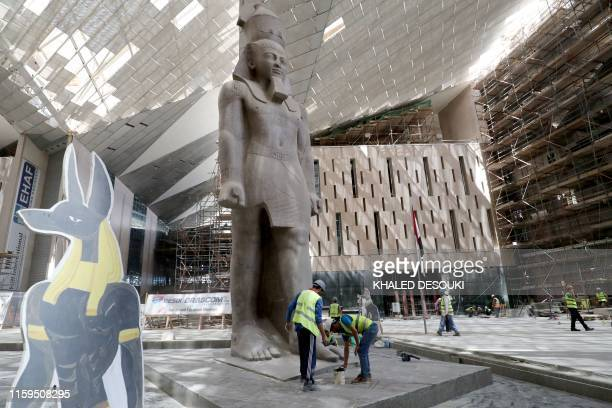 This picture taken on August 4, 2019 shows the 3,200-year-old pink-granite colossal statue of King Ramses II at the entrance of the Grand Egyptian...