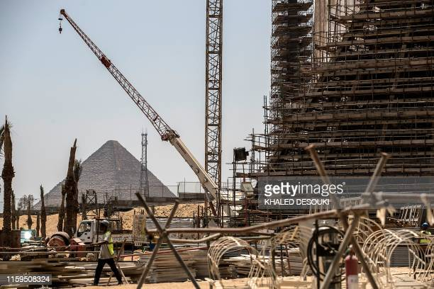 This picture taken on August 4, 2019 shows the Great pyramid of Khufu in the background of the Grand Egyptian Museum under construction in Giza on...