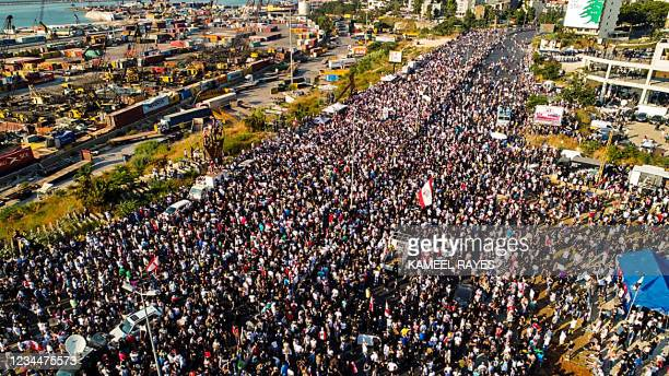 This picture taken on August 4, 2021 shows an aerial view of demonstrators gathered outside the port of Lebanon's capital Beirut on the first...
