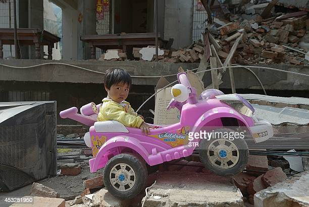 This picture taken on August 6 2014 shows twoyearold Yan Jiajia sitting on her electric toy car dug out from the debris by her father from their...