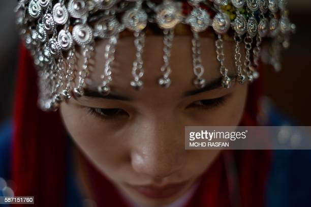This picture taken on August 6 2016 shows a Thai woman from the indigenous Akha community pictured in traditional costume before performing during a...