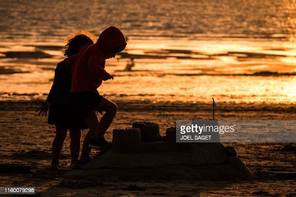 TOPSHOT This picture taken on August 6 2019 shows children playing with a sand castle on GouvillesurMer beach