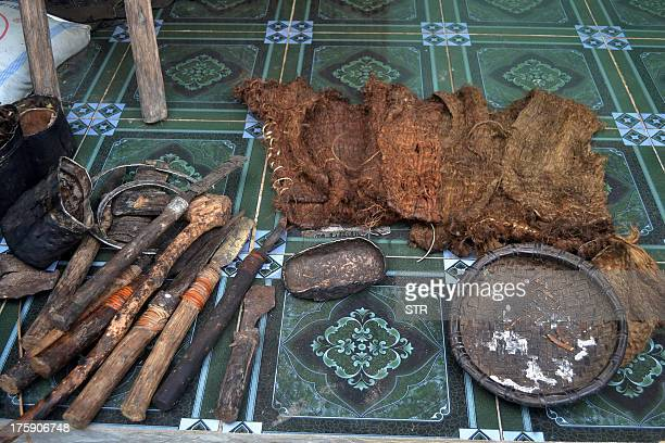 This picture taken on August 8 2013 shows handmade tools and loincloths made of tree bark that Ho Van Thanh and his son Ho Van Lang used while living...