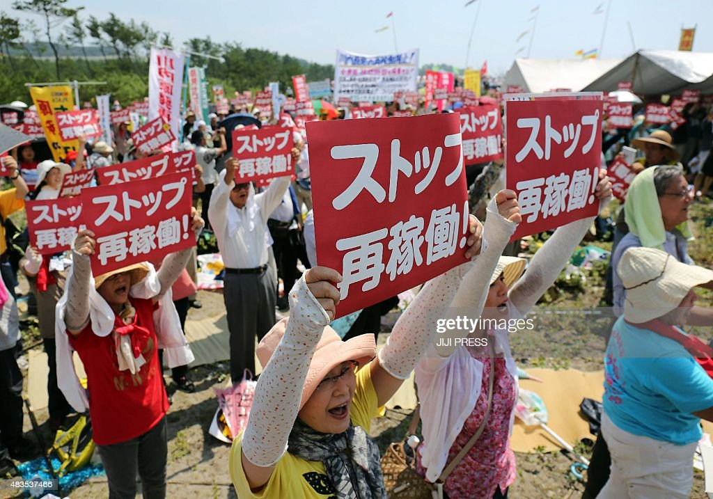 This picture taken on August 9, 2015 shows anti-nuclear protesters holding a rally against the restart of a nuclear reactor in front of the Kyushu Electric Power Sendai nuclear power plant in Satsumasendai, Kagoshima prefecture, on Japan's southern island of Kyushu. Japan is set to restart a mothballed nuclear reactor for the first time in two years on August 11, 2015, the operator said, as anti-atomic sentiment still runs high following the 2011 Fukushima crisis. JAPAN