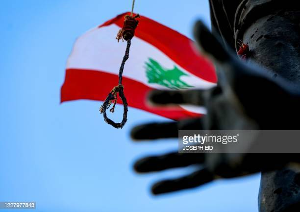 This picture taken on August 9, 2020 shows a noose and a gallows hanging from the Martyrs' Statue along with Lebanese national flags, at the Martyrs'...