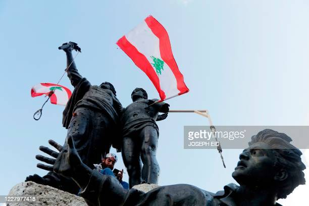This picture taken on August 9, 2020 shows nooses and a gallows hanging from the Martyrs' Statue along with Lebanese national flags, at the Martyrs'...