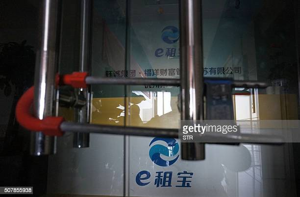 This picture taken on Dec 17 2015 shows the padlocked door of peertopeer lender Ezubao in Hangzhou in China's eastern Zhejiang province Chinese...
