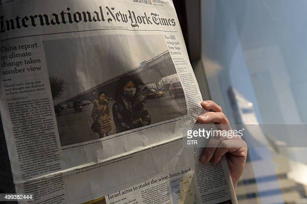 This picture taken on December 1 2015 in Bangkok shows a man reading the Asian edition of the International New York Times carrying a blank space on...