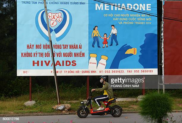 This picture taken on December 1 2015 shows a motorcyclist riding past a poster advising drug addicts to use methadone instead of used needles to...