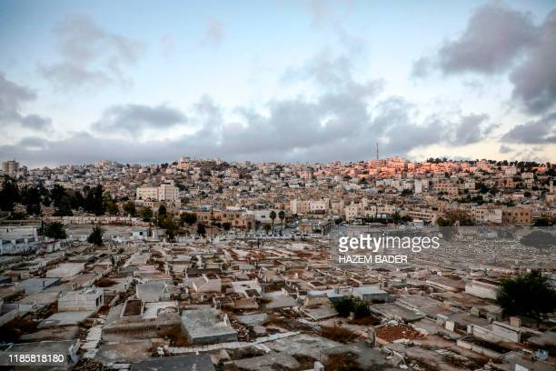 This picture taken on December 1 2019 in the flashpoint city of Hebron in the occupied West Bank shows a view of a Palestinian cemetery an old market...