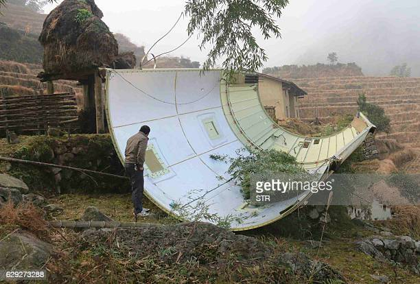CORRECTION This picture taken on December 11 2016 shows a piece of a Long March 3B rocket after it fell in a field in Suichuan County in China's...