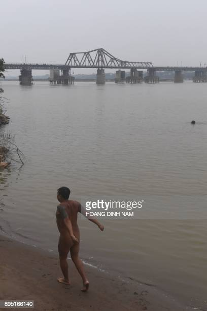 This picture taken on December 11 2017 shows a nudist walking along the southern banks of the Red River in Hanoi Butt cheeks bared Hanoi's ragtag...
