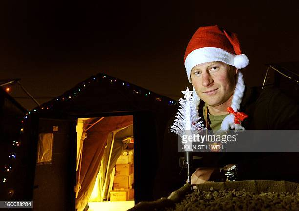 This picture taken on December 12 2012 shows Britain's Prince Harry wearing a Christmas Hat as he stands outside the VHR tent at Camp Bastion in...