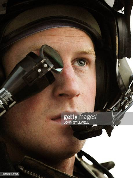 This picture taken on December 12, 2012 shows Britain's Prince Harry wearing his monocle gun sight as he sits in the front seat of his Apache...
