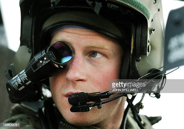 This picture taken on December 12 2012 shows Britain's Prince Harry wearing his monocle gun sight as he sits in the front seat of his Apache...