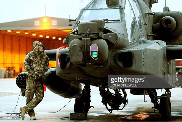 This picture taken on December 12 2012 shows Britain's Prince Harry making early mornign preflight checks around an Apache helicopter at the British...