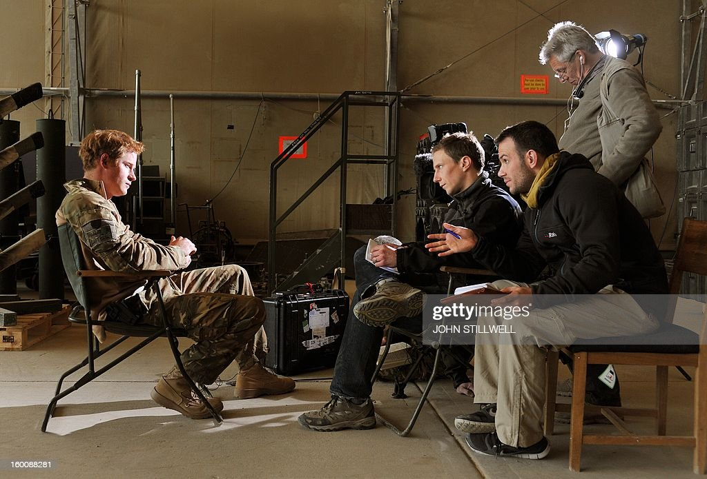 This picture taken on December 12, 2012 shows Britain's Prince Harry (L) giving an interview to a TV crew at Camp Bastion in Afghanistan's Helmand province. Prince Harry said he was 'thrilled to be back' in Britain as he returned home after serving a 20-week tour of duty in Afghanistan. The 28-year-old Apache attack helicopter co-pilot arrived back on home turf after spending two days' mandatory post-deployment 'decompression' time at a British base in Cyprus. AFP PHOTO/POOL/John STILLWELL - NOTE