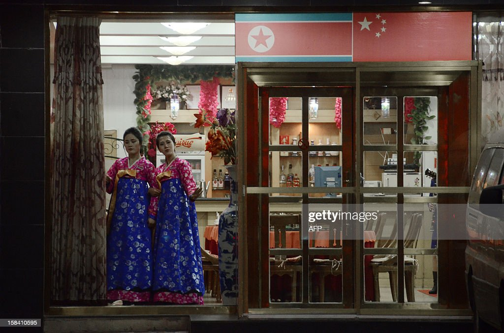 This picture taken on December 12, 2012 shows North Korean hostesses waiting for customers at the entrance to a restaurant in the Chinese border city of Dandong in China's northeastern Liaoning province. China is North Korea's biggest trading partner by far, and most of the business passes through Dandong in northeastern China, where lorries piled high with tyres and sacks are processed at the customs post.