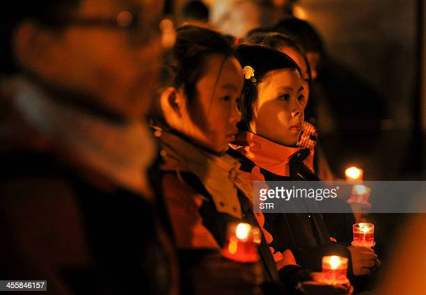 This picture taken on December 12 2013 shows young people holding candles as they attend a memorial ceremony for the victims of the Nanjing Massacre...