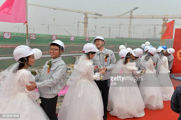 This picture taken on December 12 2016 shows workers with their brides during a group wedding ceremony at the construction site of the new airport in...