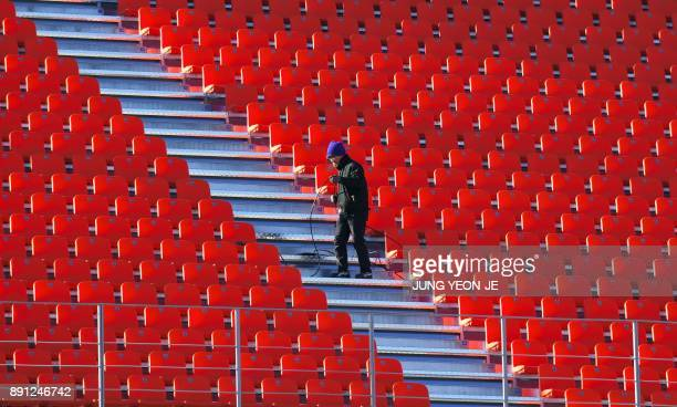 TOPSHOT This picture taken on December 12 2017 shows a South Korean worker setting up a cable at the Olympic Stadium the venue of the opening and...