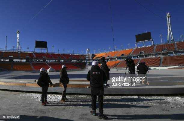 This picture taken on December 12 2017 shows South Korean workers and media members during a visit of South Korean Defence Minister Song YoungMoo to...