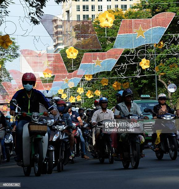 This picture taken on December 13 2014 shows motorcyclists riding under newly installed electrical decorative lighting in forme of Vietnamese...