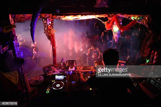 This picture taken on December 13 2016 shows partygoers dancing in front of a DJ booth during a Jungle Party on Ko Phangan island in the southern...