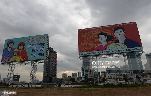 This picture taken on December 14 2014 shows large propaganda posters displayed on the bank of the Saigon River opposite the central district of Ho...