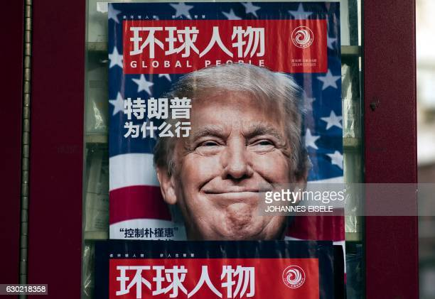 This picture taken on December 14 2016 shows a advertisement for a magazine featuring US Presidentelect Donald Trump on the cover at a news stand in...