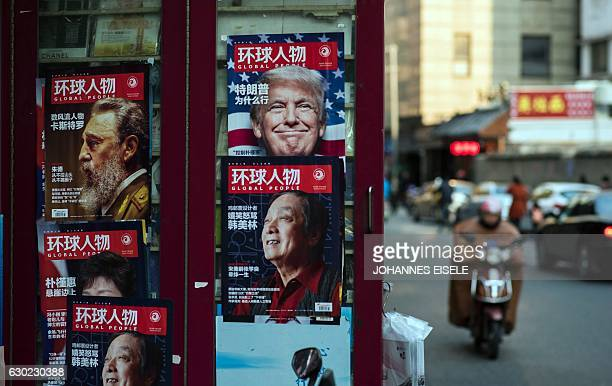 This picture taken on December 14 2016 shows an advertisement for a magazine featuring US Presidentelect Donald Trump on the cover at a news stand in...