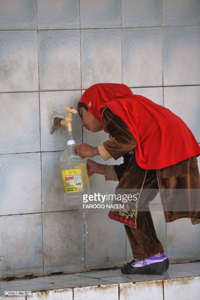 This picture taken on December 14 2017 shows a girl filling a bottle at a water filtration plant in Islamabad More than twothirds of households drink...