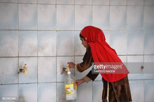 TOPSHOT This picture taken on December 14 2017 shows a girl filling a bottle at a water filtration plant in Islamabad More than twothirds of...