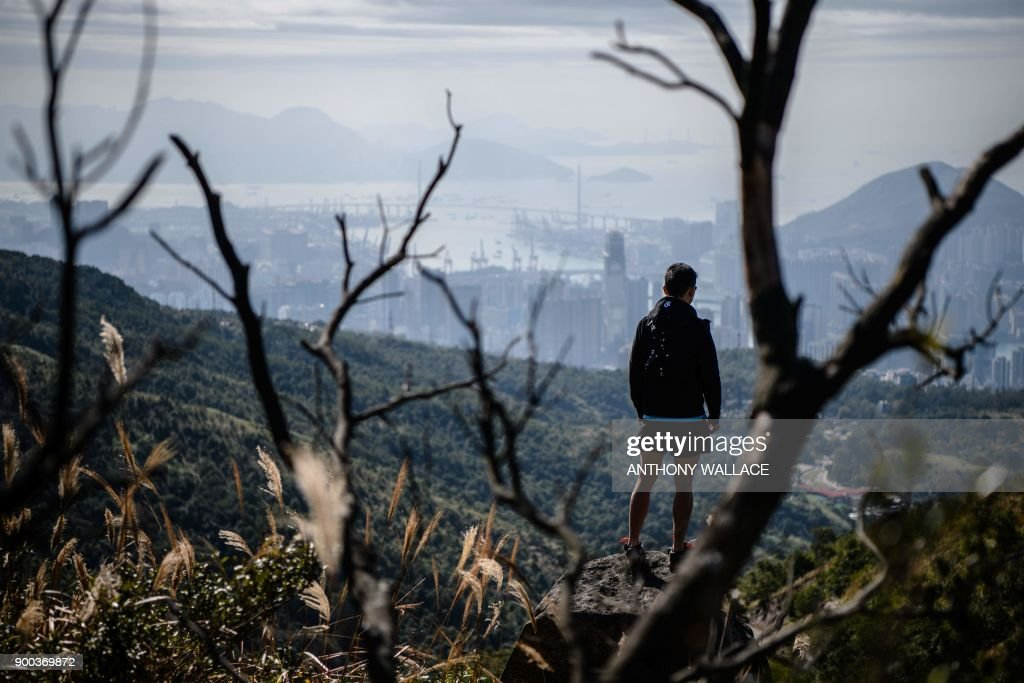 This picture taken on December 14, 2017 shows trail runner Stone Tsang, 39, looking at the city from Hong Kong's highest peak Tai Mo Shan. Wooded hillsides, craggy ridges and wheeling birds of prey are a world away from Hong Kong's famous skyscrapers but the city's country parks are a necessary balm for its stressed out residents. / AFP PHOTO / Anthony WALLACE / TO GO WITH Hong Kong-lifestyle-environment-nature-hiking-running, FEATURE by Laura MANNERING