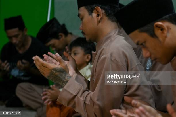 This picture taken on December 14 2019 shows pencak silat practitioners a martial art indigenous to Southeast Asia praying ahead of a practice...