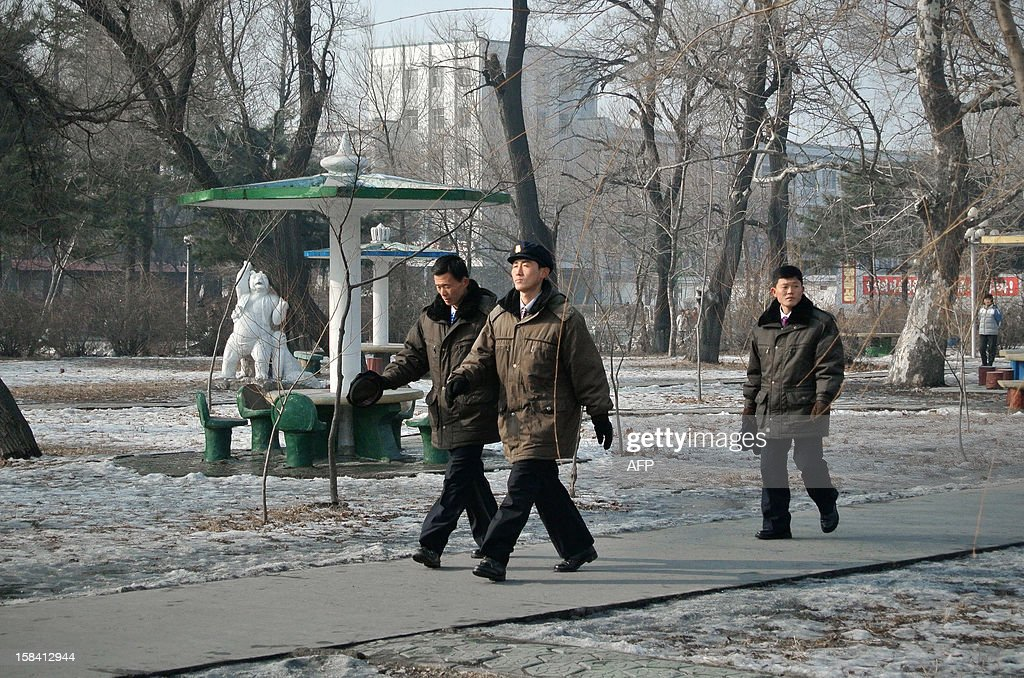 This picture taken on December 15, 2012 shows a group of North Korea workers making their way along a path after finishing work in the North Korean border town of Siniuju, across from China's northeastern city of Dandong. China is North Korea's biggest trading partner by far, and most of the business passes through Dandong in northeastern China, where lorries piled high with tyres and sacks are processed at the customs post.