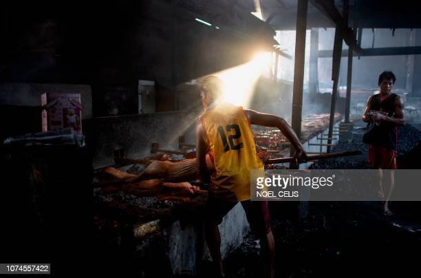 This picture taken on December 16 2018 shows lechoneros workers roasting pigs in a pit in Manila Row upon row of pigs on bamboo spits sizzle slowly...