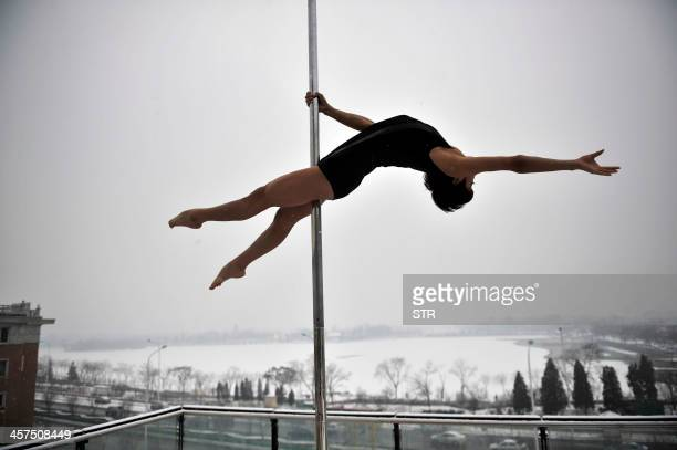 This picture taken on December 17 2013 shows a pole dancer practising after it snowed in Tianjin during a promotional event by members of China's...