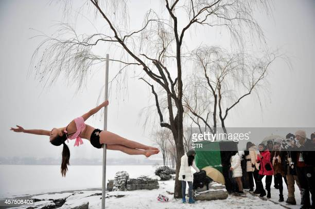This picture taken on December 17 2013 shows people watching a pole dancer practise after it snowed in Tianjin during a promotional event by members...