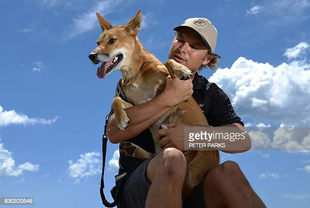 This picture taken on December 17 2016 shows James Bornstein with his pet Dingo named Kimba during her daily walk on a beach on the outskirts of...