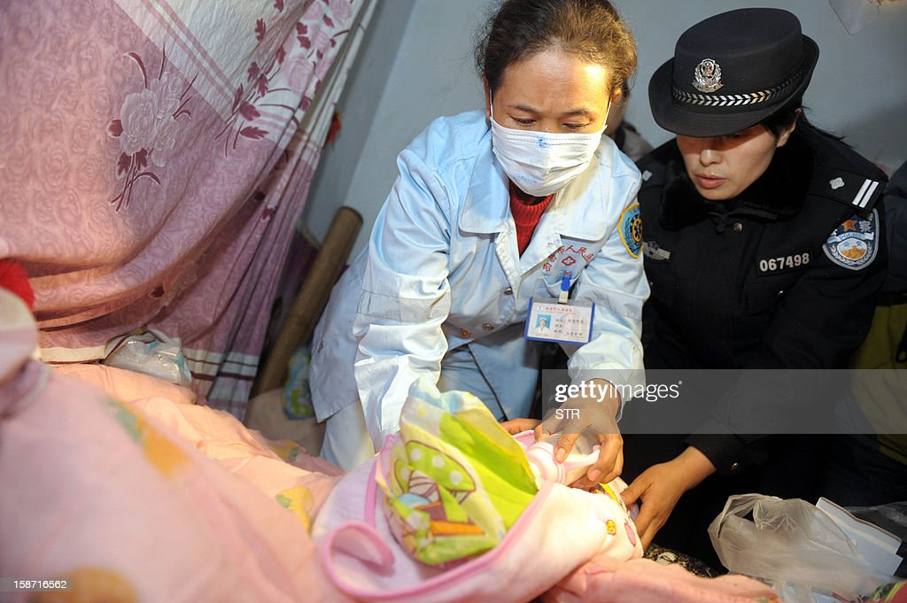 This picture taken on December 18, 2012 shows a medic (L) and a policewoman examining a rescued baby in Xichang, southwest China's Sichuan province. Police have detained two officials, including a family planning functionary, in China's latest crackdown on child-trafficking that has ensnared 355 suspects, state media said December 26. CHINA