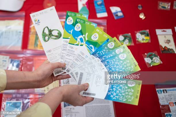 This picture taken on December 18, 2020 shows Olympic super-fan Kyoko Ishikawa holding tickets from previous Olympics Games she attended, at her...