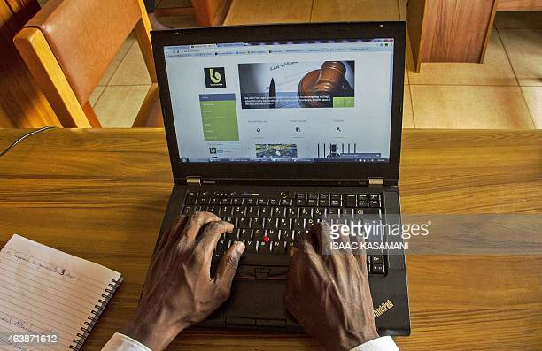 This picture taken on December 19 2014 shows the hqnds of Gerald Abila the Managing Director of Barefoot Lawyers working at his office in Kampala...